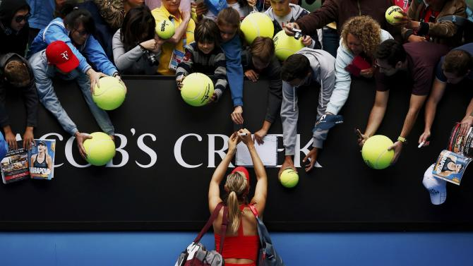Sharapova of Russia signs autographs after defeating Bouchard of Canada in their women's singles quarter-final match at the Australian Open 2015 tennis tournament in Melbourne