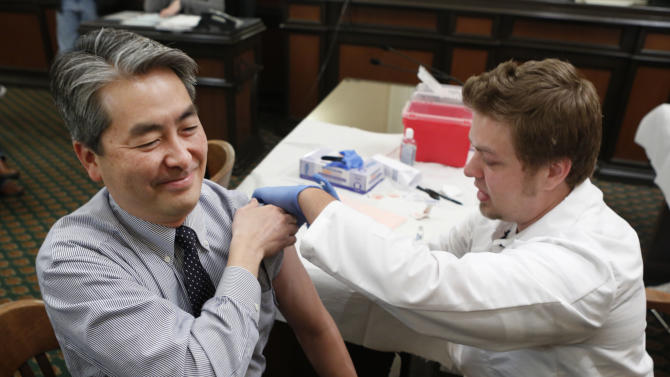 FILE - In this Monday, Jan. 28 , 2013 file photo, Assemblyman Al Muratsuchi, D-Torrance, reacts as he receives a flu shot from Tyler Poncy, a licensed vocational nurse during a free flu vaccine clinic at the Capitol in Sacramento, Calif. Health officials say the worst of the flu season appears to be over. The number of states reporting intense or widespread flu dropped again in late January 2013. The Centers for Disease Control and Prevention released the latest flu numbers on Friday, Feb. 8, 2013. (AP Photo/Rich Pedroncelli)