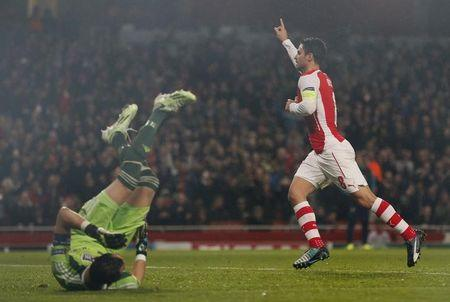 Arsenal's Arteta celebrates after scoring against Anderlecht's goalkeeper Proto during their Champions League soccer match at the Emirates stadium in London