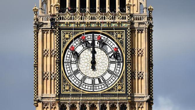Technicians carry out cleaning and maintenance work on one of the faces of the Great Clock atop the landmark Elizabeth Tower that houses Big Ben, attached to the Houses of Parliament, in London, on August 19, 2014