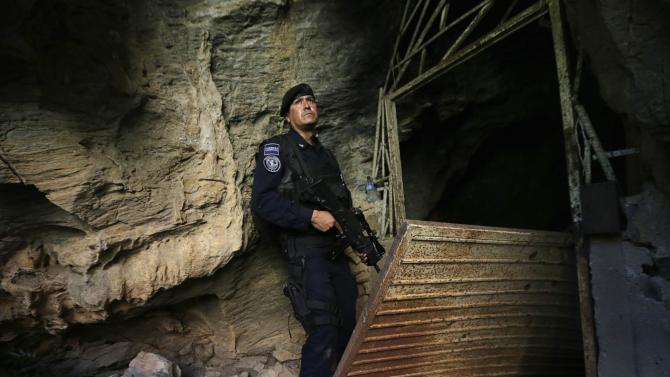 "A federal police officer stands guard outside a cave, where Servando ""La Tuta"" Gomez used to hide, during a media tour in Arteaga"