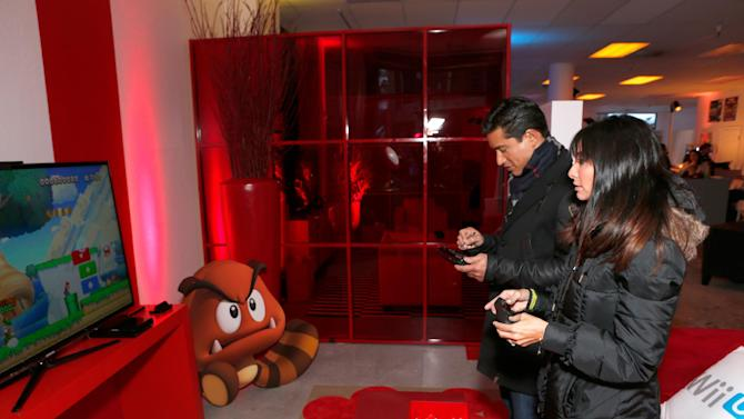 Mario Lopez, left, and Courtney Laine Mazza warm up and check out Wii U at the Nintendo Lounge while playing Nintendo Land during a break from the Sundance Film Festival on Friday, January 18, 2013 in Park City, UT. (Photo by Todd Williamson/Invision for Nintendo/AP Images)