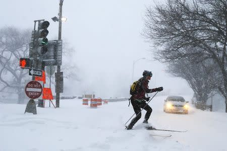 A woman cross country skis on snow covered roads during a winter blizzard in Boston