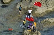 Pro-China activists carrying Chinese and Taiwanese national flags land on the disputed islands in the East China Sea on August 15. Often testy Japan-China ties took a turn for the worse in August when pro-Beijing activists landed on one of the islands