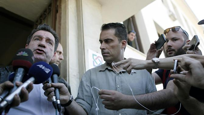 Athens' Mayor Giorgos Kaminis, left, answers questions to the media outside a municipal food distribution center in Athens, on Thursday, May 2, 2013.  An attempt by the extremist far-right Golden Dawn party to hand out free food only to Greeks, in defiance of a municipal ban was stopped by police Thursday. (AP Photo/Petros Giannakouris)