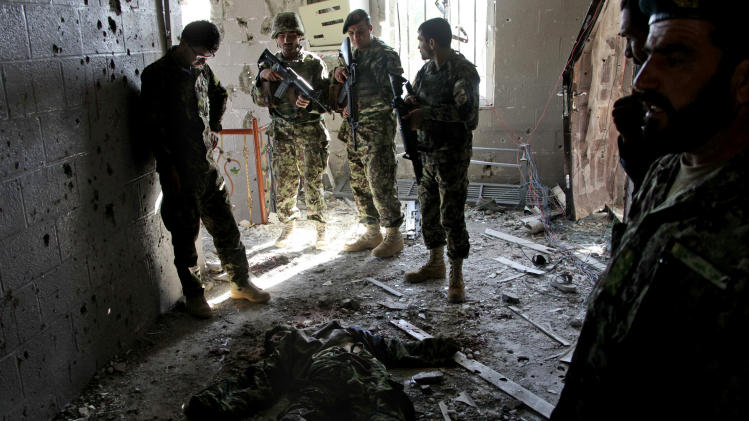 Afghan army soldiers stand around a killed Taliban, dressed as an Afghan Army soldier, in the destroyed courthouse in Farah, western Afghanistan, Thursday, April 4, 2013. Suicide bombers disguised as Afghan soldiers stormed a courthouse Wednesday in a failed bid to free more than a dozen Taliban prisoners in western Afghanistan, officials said. At least 53 people, including the nine attackers were reported killed in the fighting. The assault in Farah province was the latest example of the Taliban's ability to strike official institutions despite tight security measures. (AP Photo/Hoshang Hashimi)