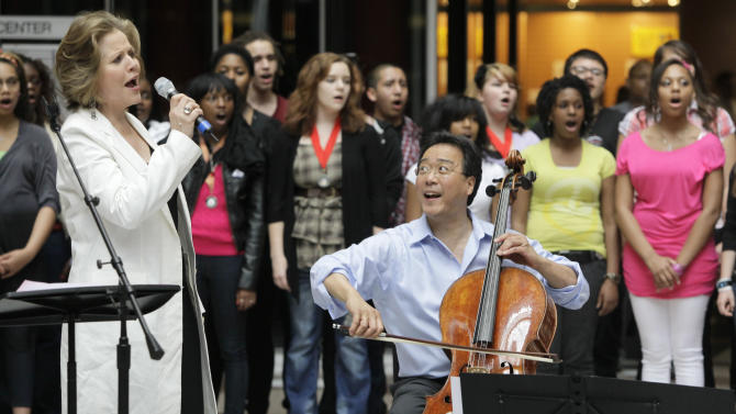 World-famous cellist Yo-Yo Ma and famed soprano Renee Fleming, left, perform with a choir of dozens of high school students in the rotunda of the State of Illinois building, the James R. Thompson Center, Monday, March 19, 2012, in Chicago. The Monday afternoon performance was to promote the Chicago Symphony Orchestra's Citizen Musician initiative. The Lyric Opera of Chicago also sponsored the event and Illinois Gov. Pat Quinn attended. (AP Photo/Kiichiro Sato)