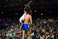 Kenya's Ezekiel Kemboi (L) and France's Mahiedine Mekhissi-Benabbad celebrate after the men's 3000m steeplechase final at the athletics event during the London 2012 Olympic Games in London