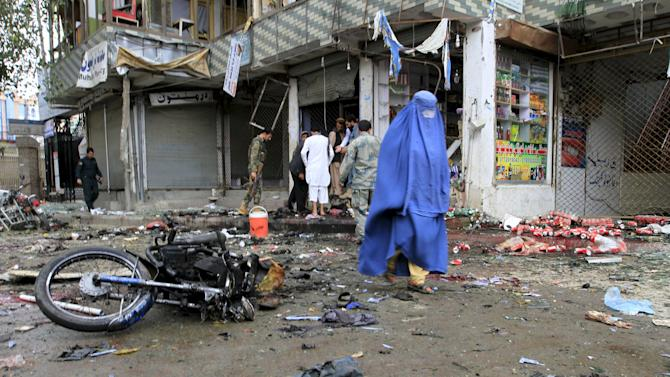 An Afghan woman walks at the site of a suicide attack in Jalalabad