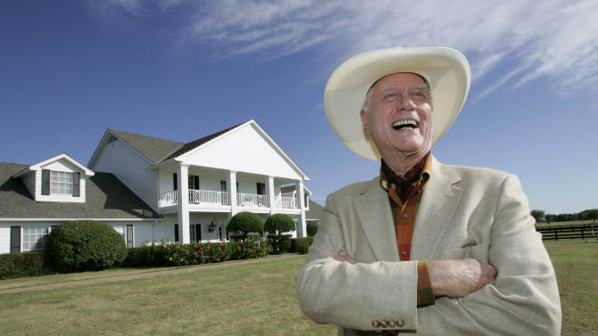 """FILE - In this Oct. 9, 2008, file photo, the late Actor Larry Hagman poses in front of the  Southfork Ranch mansion made famous in the television show, """"Dallas"""",  in Parker, Texas. Tourists have been flocking to Southfork Ranch since the early years of the classic series, which ran from 1978 to 1991. And a new """"Dallas"""" starting its second season on TNT on Monday and the recent death of the show's star, Larry Hagman, who legendarily played conniving Texas oilman J.R. Ewing, have also spurred fans to visit. (AP Photo/Tony Gutierrez, file)"""