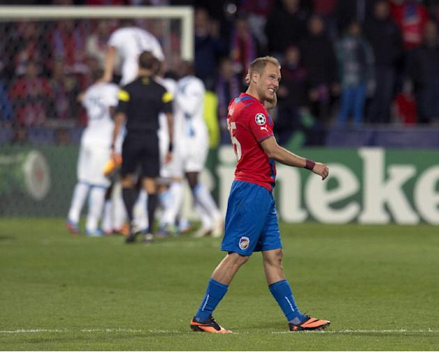 Viktoria Plzen's midfielder Daniel Kolar walks acroos the pitch  as Manchester City's players, rear, celebrate a goal during the Champion's League Group D soccer match against Viktoria Plzen in Plzen,