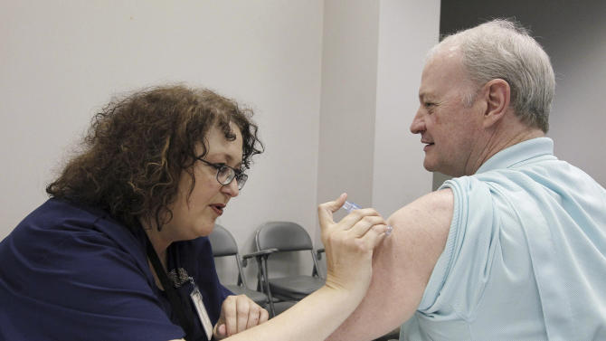 FILE - In this file photo taken Oct. 17, 2012, Bill Staples, a Mississippi Department of Health employee, is given a flu vaccine shot by registered nurse Rosemary Jones, also with the health department, in Jackson, Miss. A survey by Centers for Disease Control and Prevention researchers found that in 2011, more than 400 U.S. hospitals required flu vaccinations for their employees and 29 hospitals fired employees that were not vaccinated against the virus. (AP Photo/Rogelio V. Solis, File)