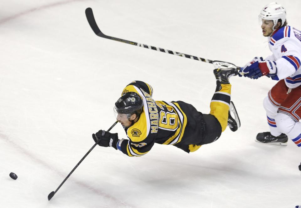 Boston Bruins left wing Brad Marchand (63) is tripped as he shoots on-goal after getting past New York Rangers defenseman Michael Del Zotto (4) during the second period in Game 1 of an NHL hockey playoffs Eastern Conference semifinal game in Boston, Thursday, May 16, 2013. (AP Photo/Charles Krupa)