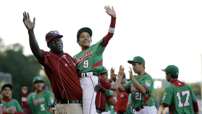 Lugazi, Uganda manager Henry Odong, left, cheers with Nuevo Laredo, Mexico's Joel Turrubiates after a pool play baseball game at the Little League World Series, Saturday, Aug. 18, 2012, in South Williamsport, Pa. Mexico won 12-0. (AP Photo/Matt Slocum)