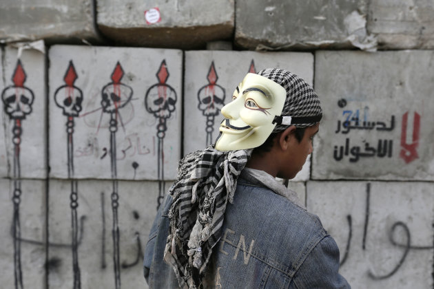 A protester looks at graffiti on cement blocks in front of the presidential palace in Cairo, Egypt, Sunday, Dec. 16, 2012. Key Egyptian rights groups called Sunday for a repeat of the first round of t