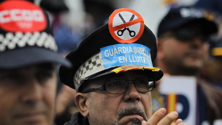 "A police officer wears a hat with a banner reading, ""Urban guards in conflict"" during a protest  against government's austerity measures and the elimination of their Christmas bonus pay, one of 14 paychecks that most Spanish civil servants get each year, in Madrid, Spain, Saturday, Nov. 17, 2012. (AP Photo/Andres Kudacki)"