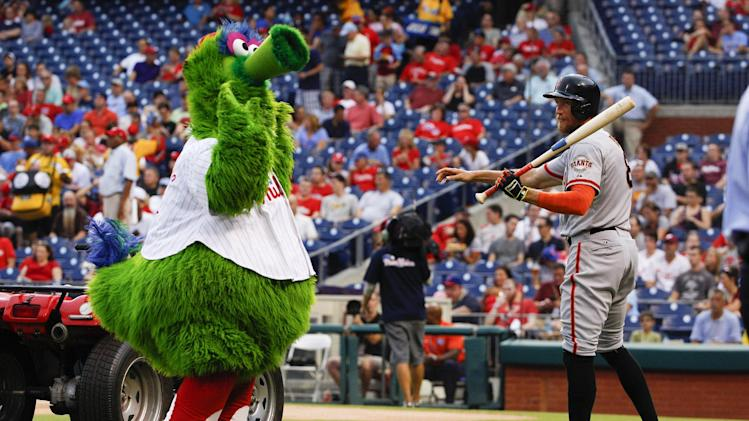 San Francisco Giants' Hunter Pence, right, looks on while dealing with the Phillie Phanatic, left, prior to the first inning of a baseball game against the Philadelphia Phillies, Wednesday, July 23, 2014, in Philadelphia. (AP Photo/Chris Szagola)