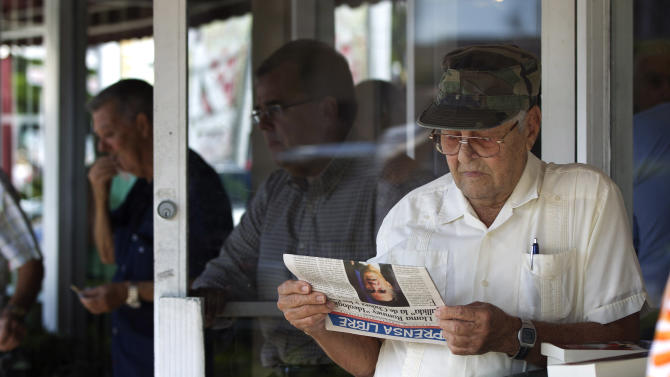 Nino Diaz reads a Spanish language newspaper at a Cuban cafe in Miami's Little Havana section, Tuesday, Oct. 16, 2012 about the news of the day. The Cuban government has announced that it will no longer require islanders to apply for an exit visa, eliminating a much-loathed bureaucratic procedure that has been a major impediment for many seeking to travel overseas for more than a half-century. A notice published in Communist Party newspaper Granma said the change takes effect Jan. 14, and beginning on that date islanders will only have to show their passport and a visa from the country they are traveling to. It is the most significant advance this year in President Raul Castro's five-year plan of reform that has already seen the legalization of home and car sales and a big increase in the number of Cubans owning private businesses.(AP Photo/J Pat Carter)