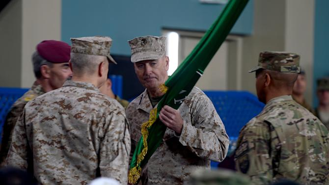 U.S. Marine Gen. Joseph F. Dunford, center, receives a flag from outgoing ISAF commander, U.S. Gen. John Allen, left facing away from camera, after taking over as new commander of NATO in Afghanistan during a change of command ceremony at the ISAF headquarters in Kabul, Afghanistan, Sunday, Feb. 10, 2013. Dunford takes charge at a critical time for President Barack Obama and the military as foreign combat forces prepare to withdraw by the end of 2014. (AP Photo/Massoud Hossaini, Pool)