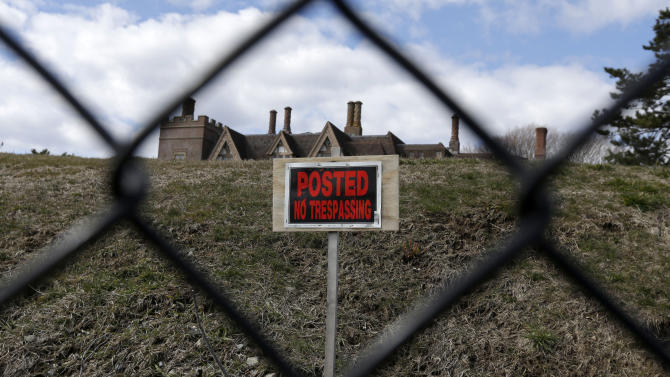 """FILE - In this Wednesday, March 27, 2013 file photo a """"no trespassing"""" sign and the roof of a mansion are visible from the path of the Cliff Walk, in Newport, R.I. Large portions of the Cliff Walk damaged by Superstorm Sandy have yet to be repaired as the summer tourist season approaches. (AP Photo/Steven Senne, File)"""