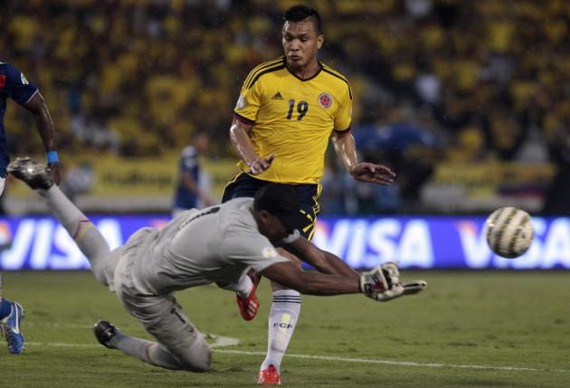Ecuador's goalkeeper Banguera makes a save on the ball under pressure from Colombia's Gutierrez during a 2014 World Cup qualifying soccer match in Barranquilla