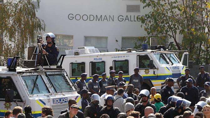 South Africa's riot police officers stand guard as ruling party supporters sing during their protest in Johannesburg, South Africa on Tuesday May 29, 2012. The African National Congress and its alliance partners march to the Goodman Gallery to protest against a now-defaced painting depicting President Jacob Zuma. (AP Photo/Themba Hadebe)