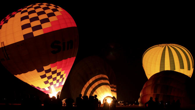 FILE - In this Friday, Nov. 23, 2012 file photo, tourists wait their turns to ascend in hot air balloons before sunrise in Luxor, Egypt. On Sunday senior civil aviation official says Egypt has resumed hot air balloon sightseeing flights in the ancient city of Luxor in southern Egypt, weeks after a fiery accident. (AP Photo/Nariman El-Mofty, File)