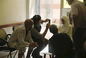 A U.N. chemical weapons expert takes a picture of a person affected by an apparent gas attack, at a hospital where she is being treated, in the Damascus suburb of Zamalka
