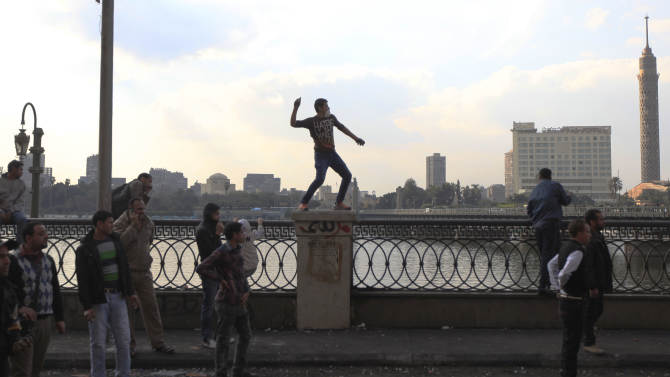 Pro and anti- government protesters clash near Tahrir Square, Cairo, Egypt, Tuesday, Jan. 29, 2013. Intense fighting for days around central Tahrir Square engulfed two landmark hotels and forced the U.S. Embassy to suspend public services on Tuesday. (AP Photo/Khalil Hamra)