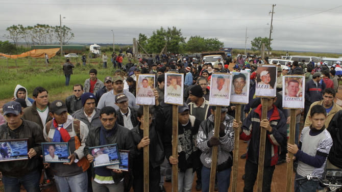 Farmers protest holding pictures of people who died on June 15 during clashes with police as they were evicted from a reserve, on the outskirts of Curuguaty, Paraguay, Thursday, June 21, 2012. The lower house of Paraguay's congress has voted to begin impeachment proceedings against Paraguay's President Fernando Lugo for his role in the violent eviction, after Lugo was heavily criticized over the land eviction last week that killed 17 people in gunbattles between police and landless farmers in a forest reserve. (AP Photo/Jorge Saenz)
