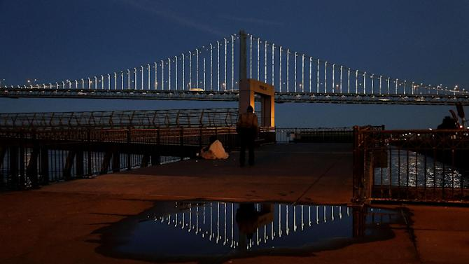 In this Wednesday, Feb. 20, 2013,  photo, lights  are reflected on the San Francisco-Oakland Bay Bridge on Pier 14 in San Francisco. The San Francisco-Oakland Bay Bridge has been turned into the latest, and by far the biggest, backdrop for New York artist Leo Villareal, who has individually programmed 25,000 white lights spaced a foot apart on 300 of the span's vertical cables to create what is being billed as the world's largest illuminated sculpture. (AP Photo/Jeff Chiu)