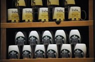 Starbucks coffee mugs are on display at the country's first outlet in Mumbai on October 19. Starbucks, the world's biggest coffee chain, launched its first Indian outlet Friday in an upscale part of Mumbai, becoming the latest global firm to tap the urban youth's growing taste for caffeine
