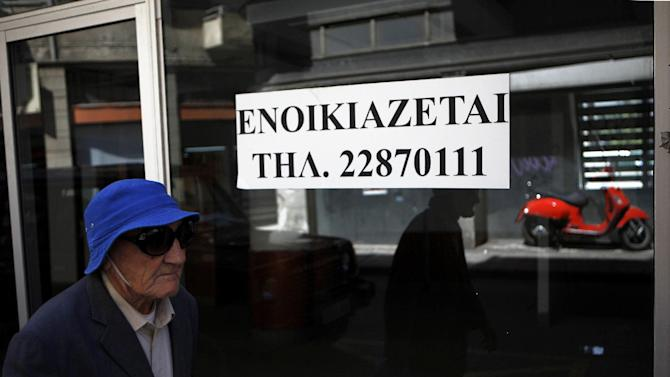"""An elderly man passes  an empty closed shop with a sign reading in Greek """" To rent"""" in central Nicosia, Cyprus, Tuesday, April 9, 2013. Last month, Cyprus agreed that bondholders, investors and savers with more than 100,000 euros in the country's two largest — and most troubled — banks will take significant losses in exchange for a 10 billion euro ($13 billion) rescue package. (AP Photo/Petros Karadjias)"""