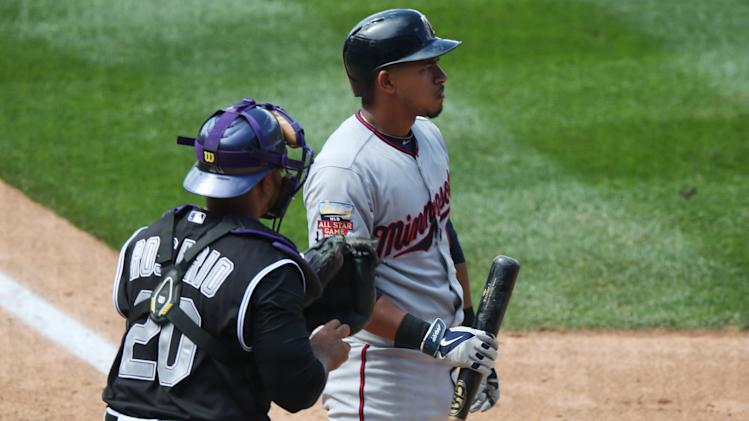 Minnesota Twins' Eduardo Escobar, back, reacts after being called out on strikes as Colorado Rockies catcher Wilin Rosario looks on in the fifth inning of an interleague baseball game in Denver on Sunday, July 13, 2014. (AP Photo/David Zalubowski)