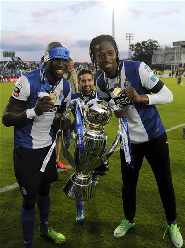 FC Porto's Eliaquim Mangala, left, from France and Abdoulaye Ba, from Senegal, with Joao Moutinho at behind, celebrate with the trophy after their 2-0 victory over Pacos Ferreira in the last match of 