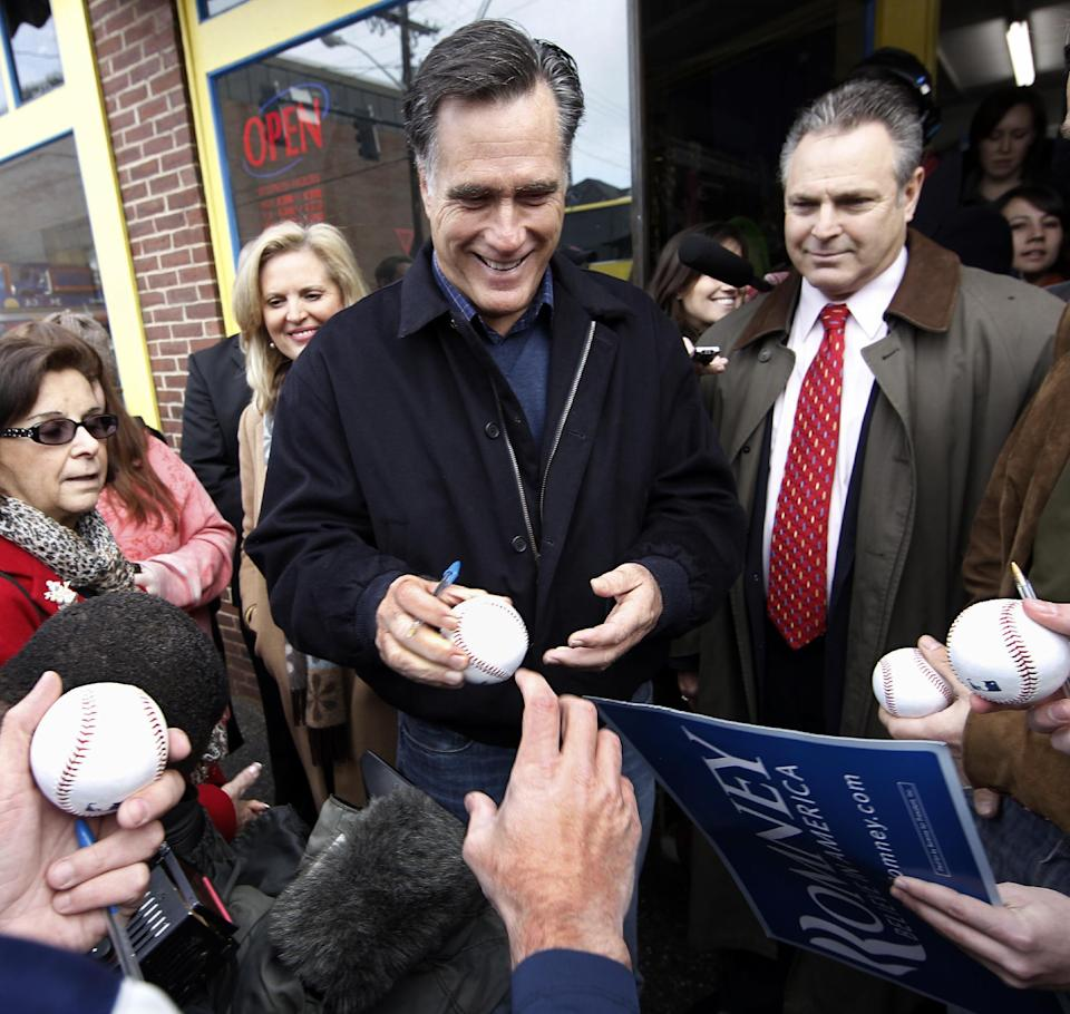 Republican presidential candidate, former Mass. Gov. Mitt Romney signs baseballs while campaigning in Concord, N.H. Friday, Dec. 23, 2011. (AP Photo/Winslow Townson)