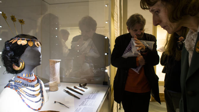 People look to a reconstructed head of a Sumerian woman during a media preview of the exhibition ' Uruk  5,000 Years of the Megacity' at the Pergamon Museum Berlin, Wednesday, April 24, 2013. Berlin's Pergamon Museum is offering visitors a glimpse of perhaps the world's first real metropolis in a new exhibition that traces the long history of Uruk, in present-day Iraq. The show marks a century of excavations at Uruk. But even now, organizers say that only about 4.5 percent of the sprawling site in the Iraqi desert has been explored. (AP Photo/Markus Schreiber)