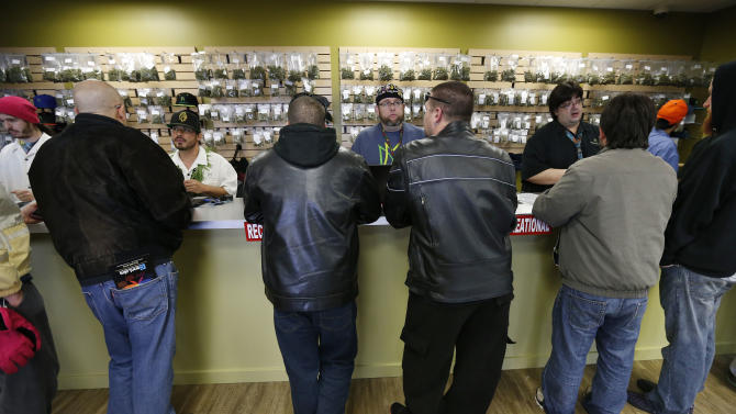 FILE - In this Jan. 1, 2014 file photo, employees help customers at the crowded sales counter inside the Medicine Man marijuana retail store, in Denver. A group of marijuana activists want another pot vote in Colorado, to loosen restrictions on who can have it. A proposed ballot measure up for state review Wednesday Jan. 14, 2014 would end criminal penalties for cannabis possession. If approved, the measure would effectively discard Colorado's 1-ounce possession limit and 21-and-over restriction. (AP Photo/Brennan Linsley, File)