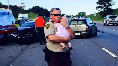 Sheriff's Deputy Gently Cradles Baby Girl on the Side of the Road After Crash