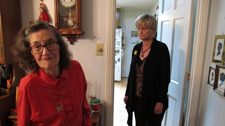 In this Thursday, April 19, 2012 photo, Miriam Parker and her daughter Donna stand in the dining room of her Raleigh, N.C., home. Donna Parker and her siblings struggled for nearly seven years to extricate her parents from the clutches of an international sweepstakes scam. (AP Photo/Allen Breed)