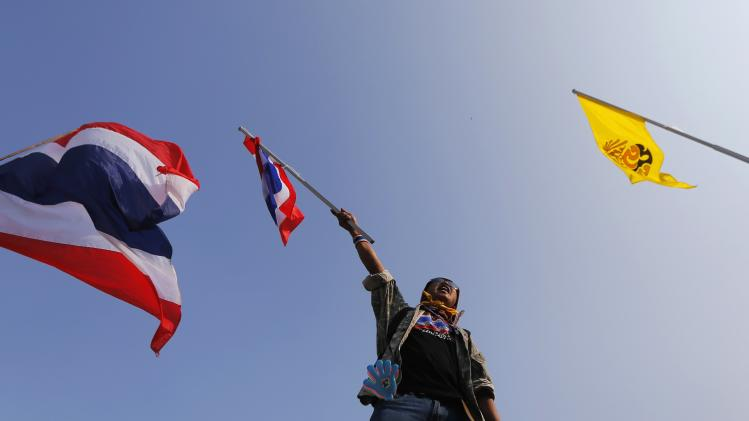An anti-government protester waves a Thai national flag from atop a barricade outside the Government House in Bangkok