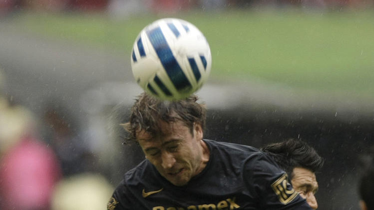Pumas' Martin Andres Romagnoli heads for the ball in front of America¥s Jesus Molina at a Mexican soccer league match in Mexico City, Saturday, Aug. 30, 2014. (AP Photo/Christian Palma)