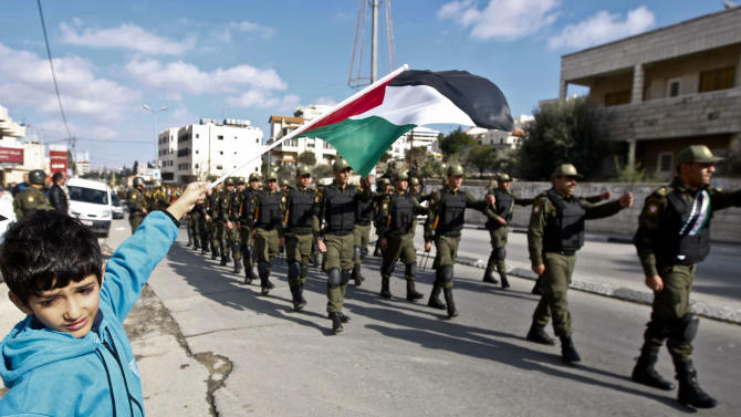 A Palestinian youth waves a flag as security officers march in support of Palestinian President Mahmoud Abbas, and to celebrate their successful bid to win U.N. statehood recognition the in the West bank city of Bethlehem, Monday, Dec. 17, 2012. (AP Photo/Majdi Mohammed)
