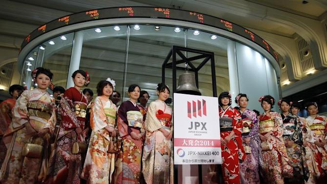 Women, dressed in ceremonial kimonos, pose in front of an electronic board showing stock prices after the New Year opening ceremony at the TSE, held to wish for the success of Japan's stock market, in Tokyo