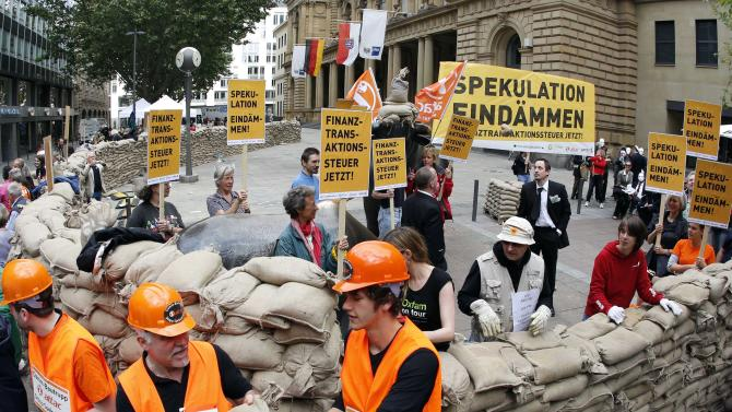 """In this picture taken with a fisheye lens, protesters,  build a wall around the Frankfurt stock exchange with  sandbags to demonstrate against sthe current financial policy in Frankfurt, central Germany, Sunday June 17, 2012. Poster at right reads: Stem Speculations,  and  others : Transaction Tax  Now.   Activists calling for a tax on financial transactions have erected a wall of sandbags outside the Frankfurt stock exchange.The anti-globalization group Attac said that about 200 people participated in Sunday's action. Carrying placards with slogans such as """"Stem Speculation"""" and """"Financial transaction tax now,"""" they built the wall of sandbags around the statues of a bull and a bear symbols of optimistic and pessimistic markets  that stand in front of the exchange building. (AP Photo/dapd/mario Vedder)"""