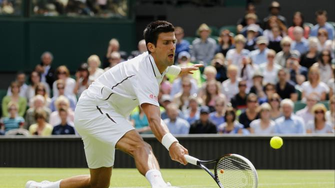 Novak Djokovic of Serbia returns the ball to Florian Mayer of Germany during a Men's first round singles match at the All England Lawn Tennis Championships in Wimbledon, London, Tuesday, June 25, 2013. (AP Photo/Sang Tan)
