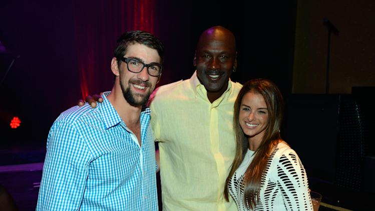 IMAGE DISTRIBUTED FOR JORDAN - From left, former U.S. Olympic swimmer Michael Phelps, Charlotte Bobcats owner Michael Jordan and fiancee model Yvette Prieto attend the Michael Jordan Celebrity Invitational opening night dinner on Wednesday, April 3, 2013 in Las Vegas. (Photo by Jeff Bottari/Invision for Jordan/AP Images)