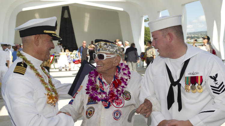 Navy chaplain Sal Aguliera, left, shares a moment with Pearl Harbor survivor Allen Bodenlos, center, who is being escorted by Navy petty officer Michael Temple aboard the USS Arizona Memorial during the ceremony commemorating the 72nd anniversary of the attack on Pearl Harbor, Saturday, Dec. 7, 2013, in Honolulu. (AP Photo/Marco Garcia)