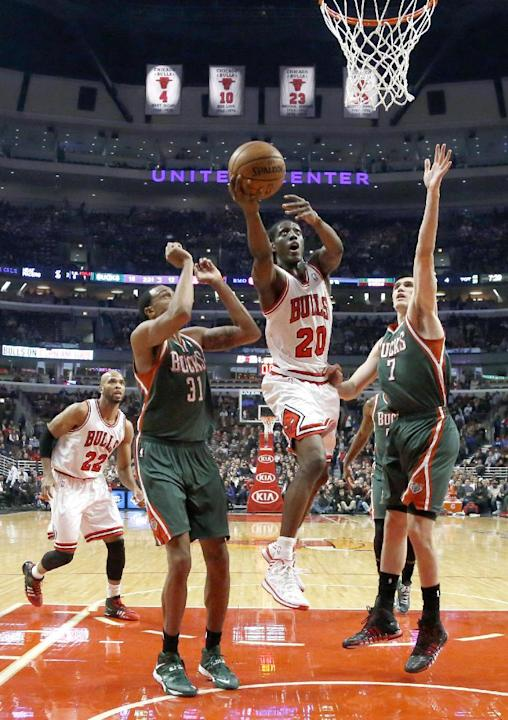 Chicago Bulls small forward Tony Snell (20) drives to the basket and scores past Milwaukee Bucks power forward John Henson (31) and Ersan Ilyasova (7) as Taj Gibson (22) is near during the first half