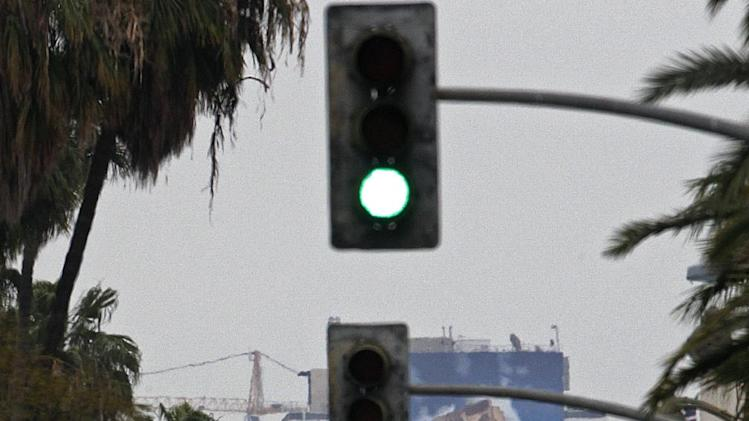 In this Wednesday, April 24, 2013 photo, traffic signals are seen on Wilshire Boulevard in Los Angeles. The nation's most congested city has become a model for traffic control. With the flip of a switch earlier this year, Los Angeles became a worldwide leader by synchronizing all of its nearly 4,400 stoplights, making it the world's first major city to do so. (AP Photo/Reed Saxon)